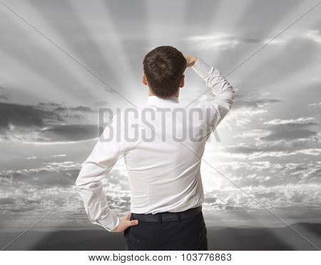 Businessman standing over sky and purposefully looking away