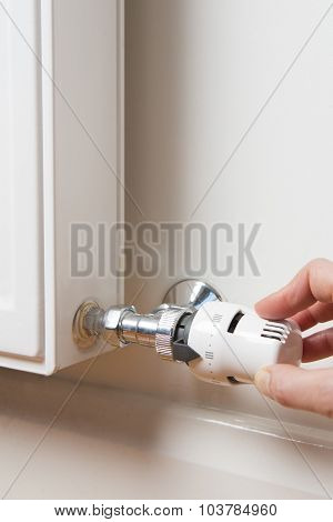Close Up Of Hand Adjusting Radiator Thermostat poster