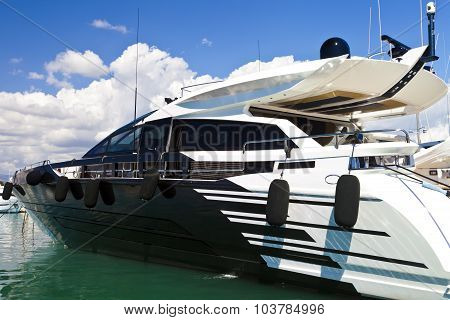 Modern luxury motor yacht in white and navy blue colours moored in a sea harbor in French Riviera Me