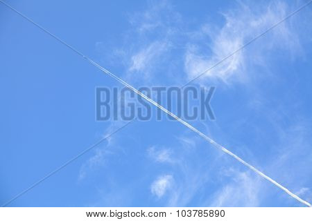 Airplane Contrail Against Beautiful Blue Sky With Delicate Clouds.