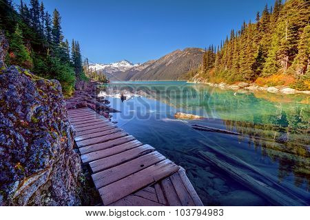 Wooden walkway on the side of the blue-green waters and pine trees, with snow-capped mountains on th