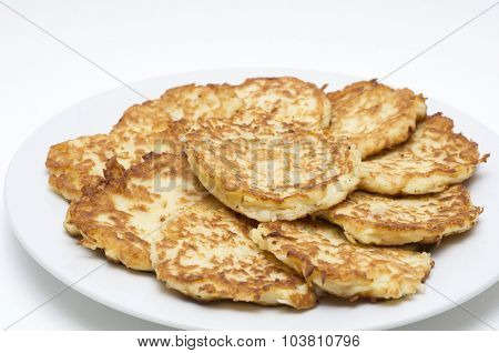 Traditional Hanukkah Potato Pancakes - Latkes - Levivot on a white plate during the Jewish Festival of Lights holiday.