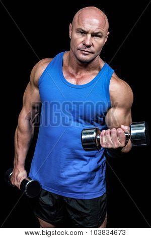 Portrait of man lifting dumbbells against black background poster