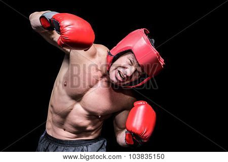Aggressive boxer puching against black background