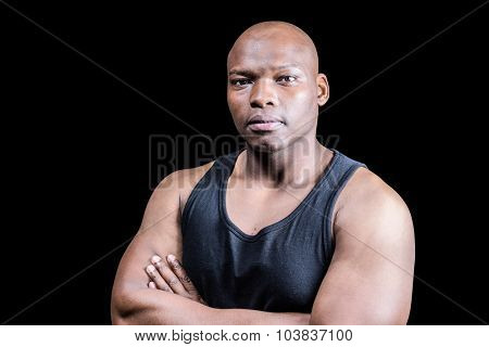 Portrait of bald bodybuilder with arms crossed against black background