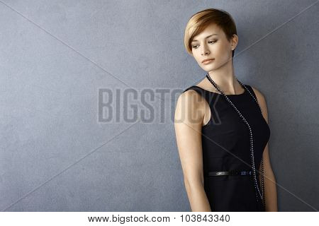 Portrait of dreamy young woman in black dress leaning to wall