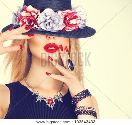 Beautiful sexy woman with red lips and manicure in modern black hat. Beauty fashion model girl with accessories- rings, bracelets, necklace and elegant hat decorated with flowers