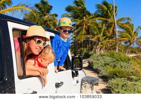 family driving off-road car on tropical beach