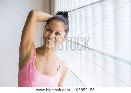 Potrait of a young latin woman indoors wearing leggins and a top, ready for her workout.