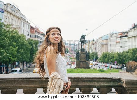Happy longhaired bohemian woman tourist sightseeing in the historical center of Prague. In the background Saint Wenceslas statue on Wenceslas Square in Prague. Tourism travel concept. poster