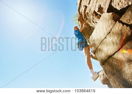 Young sportsman in activewear climbing the rock