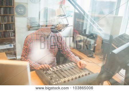 Radio host operating sound mixer in studio seen through glass
