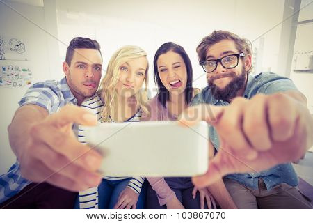 Smiling business people posing for selfie while sitting on desk in office