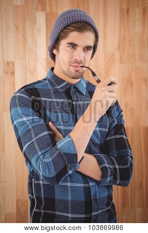 Hipster smoking pipe while standing against wooden wall