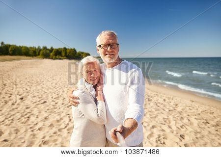 age, travel, tourism, technology and people concept - happy senior couple taking picture with smartphone selfie stick on summer beach