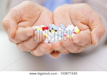 age, medicine, health care and people concept - close up of senior woman cupped hands with pills at home or hospital