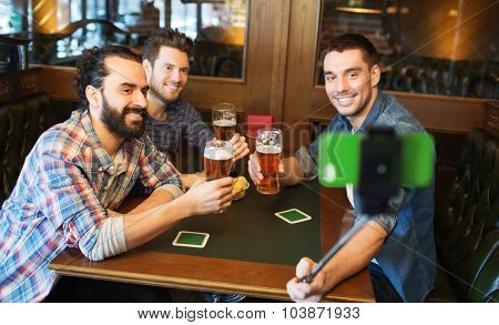 people, leisure, friendship, technology and bachelor party concept - happy male friends drinking beer and taking picture with smartphone selfie stick at bar or pub