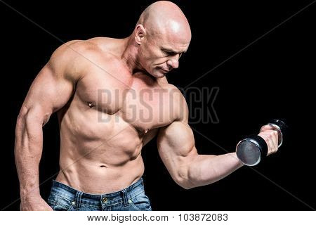 Bald man lifting dumbbells against black background