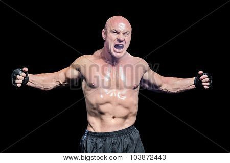 Aggressive fighter with arms outstretched against black background