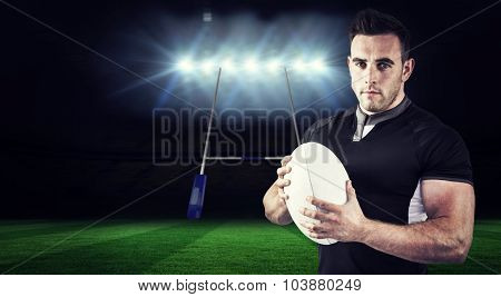 Tough rugby player looking at camera against rugby stadium