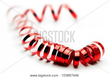 Red ribbon coil or spiraling on white surface. Red metallic ribbon isolated on white. Shallow depth of field.