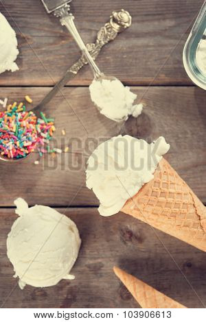 Top view scoop vanilla ice cream in waffle cone with spoon and color rice on wood background. Vintage toned.