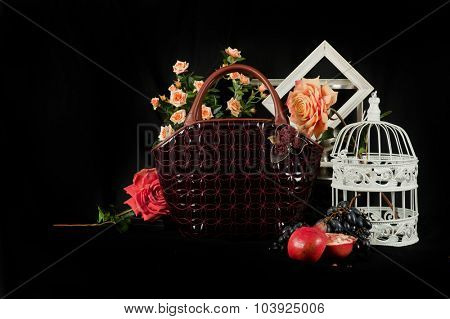 Fashionable handbag  with cage fruits and flowers on black background.