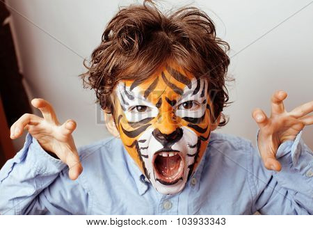 little cute boy with faceart on birthday party close up, little cute tiger