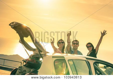 Best friends cheering by car road trip at sunset - Group of happy people outdoor on vacation tour - Friendship concept at travel with positive nostalgic emotions - Soft focus due to backlight contrast poster