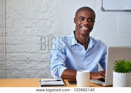 portrait of handsome African black young business man working on laptop computer at office desk