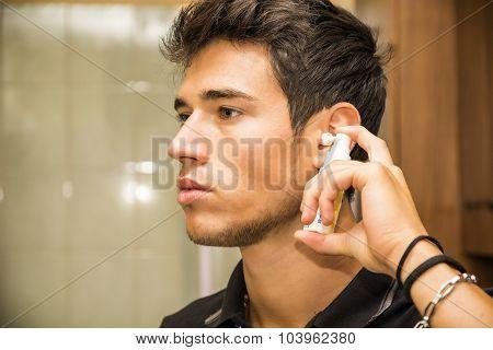 Young Man Spraying Ear Spray into Ears