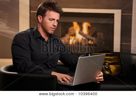 Casual Businessman Using Laptop At Home