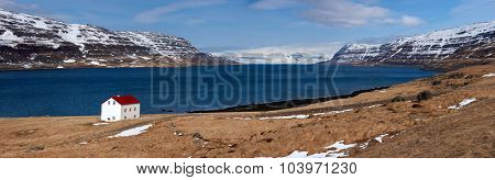 Quaint isolated farm house along the fjord westfjords surrounded by mountains covered in snow in Iceland