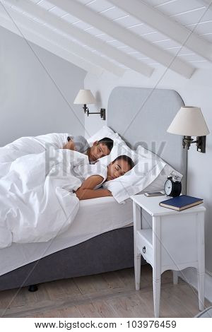 peaceful young couple sleeping comfortably in bed at home poster
