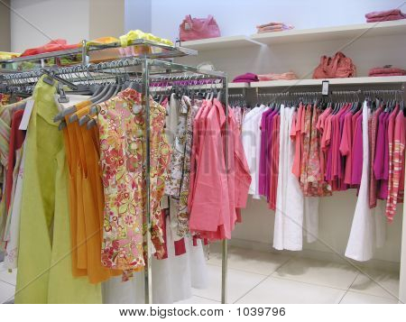 womans pink color clothes hangs in shop poster