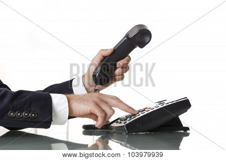 Close Up Of Businessman Hands Dialing Out On A Black Deskphone