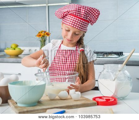 cute little gilr mixing ingredients for a dough on a kitchen