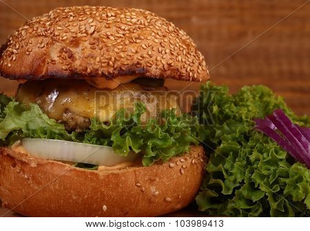 One big tasty appetizing fresh burger of green lettuce red tomato cheese bacon slice meat cutlet violet oinion and white bread bun with sesame seeds on wooden table closeup horizontal picture poster