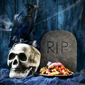 a plate with Halloween candies and an amputated finger in a dismal scene with a crow, a skull and a gravestone with the text RIP carved in poster