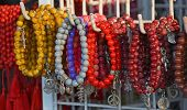 Colourful red yellow grey brown and purple Coral beads and bracelets for sale in a Legian Shop Bali Indonesia. poster