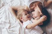 Young mother with her 2 years old son dressed in pajamas are relaxing and playing in the bed at the weekend together, lazy morning, warm and cozy scene. Pastel colors, selective focus, top view. poster