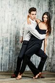 Beautiful young couple in love dancing tango with passion. Professional dancers. Latino dancers. poster