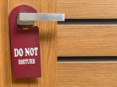 Do Not Disturb door hanger hanging on hotel room door handle poster