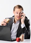 Busy hardworking business man eats lunch at his desk while working and talking on his mobile cell phone poster