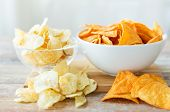 fast food, junk-food, cuisine and eating concept - close up of crunchy potato crisps and corn crisps or nachos in bowls poster