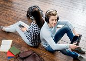 Girl using a smartphone and boy using a tablet in headphones listening to the music and leaning on each other on wooden floor having notebooks and bags around them.   poster