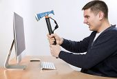 Crazy man is going destroy his computer desktop with iron axe threatening it as hummer into big screen smart casual dress office background keyboard mouse poster