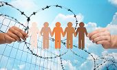 crime, imprisonment, refugee and humanity concept - multiracial couple hands holding chain of paper people pictogram over blue sky and barb wire background poster