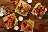 many different flavored buffalo chicken wings with beer party sampler sharing platter shot from top down view poster