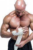 Fighter tying bandage on hand against white bakground poster